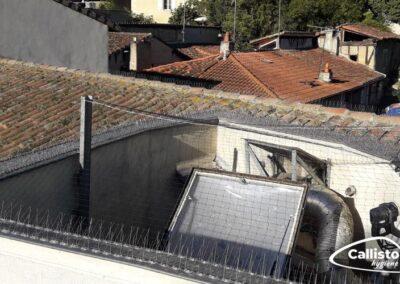 Pics et grilles anti-pigeons au dessus d'un cour intérieur